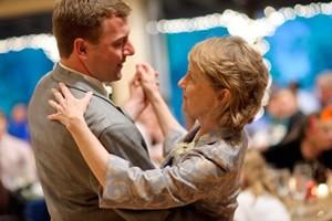 Homem e sua sogra dançando juntos, vistos de perfil.