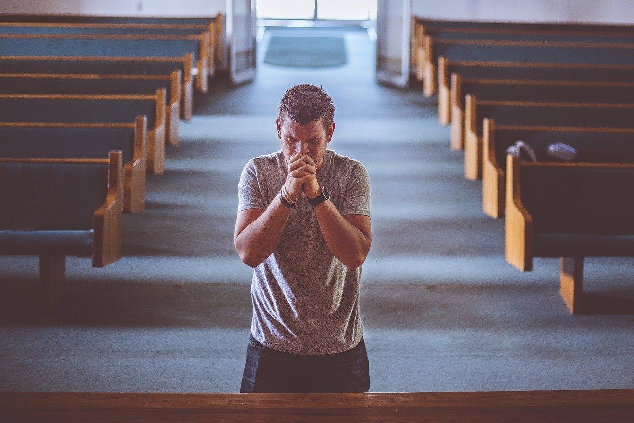 Homem no altar de uma igreja, com os dedos das mãos entrelaçados em frente de sua boca, e os olhos fechados.
