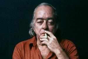 Vinicius de Moraes fumando cigarro visto de frente em fundo preto