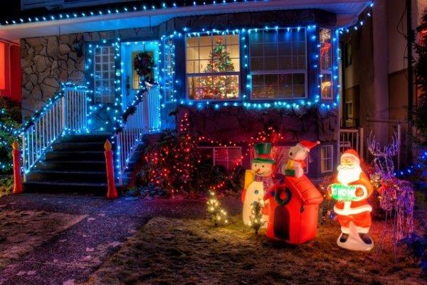 Fachada de casa decorada com luzes coloridas e estátuas natalinas.