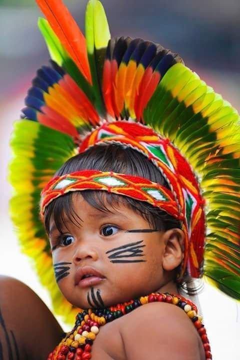 Bebê indígena com adereços tradicionais e pinturas na pele