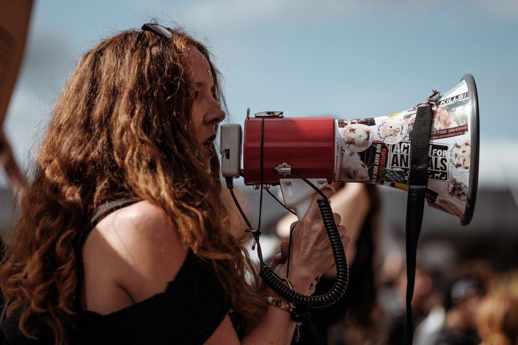 Mulher protestando com um megafone.
