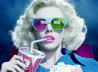 Mulher com óculos 3D em cinema, segurando um saco de pipoca e um copo de refrigerante.