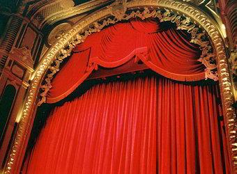 Palco de teatro com cortina vermelha fechada.