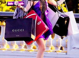 Mulher segurando muitas sacolas de compras de marcas famosas.