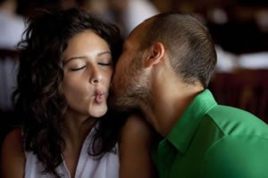 Homem dando beijo em bochecha de mulher
