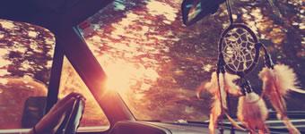 Carro no ponto de vista do passageiro da frente. O sol está se pondo e pendurado no retrovisor se encontra um apanhador de sonhos.