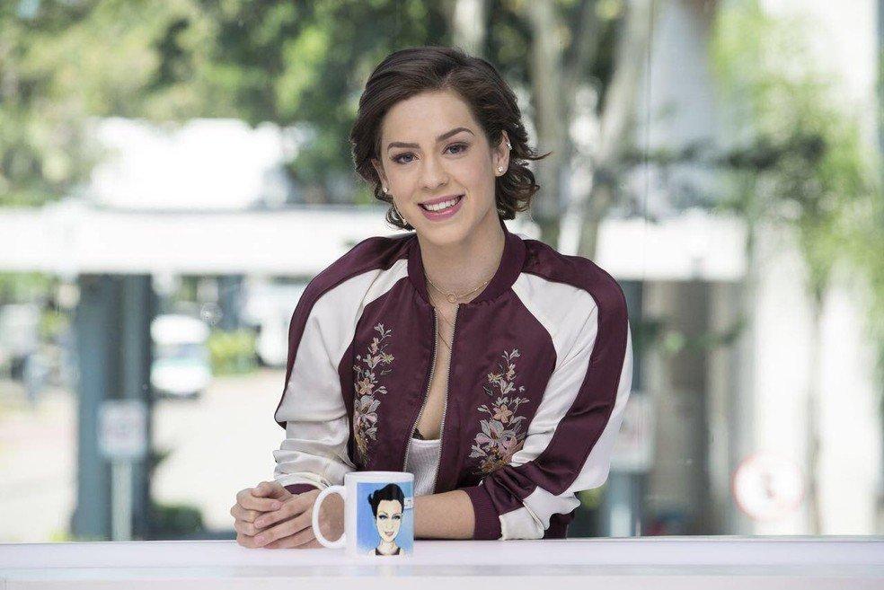 Mulher olhando para frente e sorrindo apoiada em uma mesa