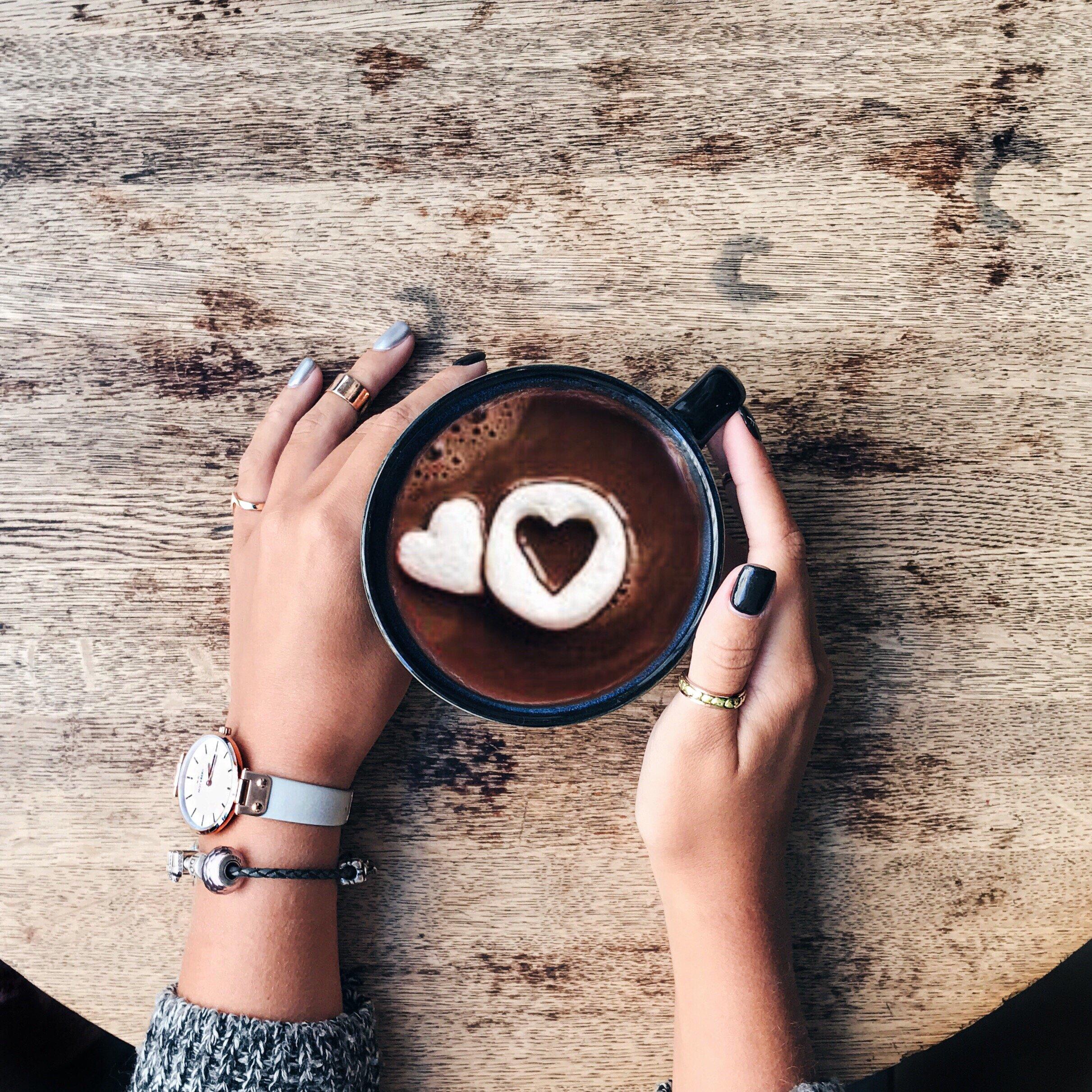 Mãos de mulher segurando xícara de chocolate quente que tem chocolates em formato de coração