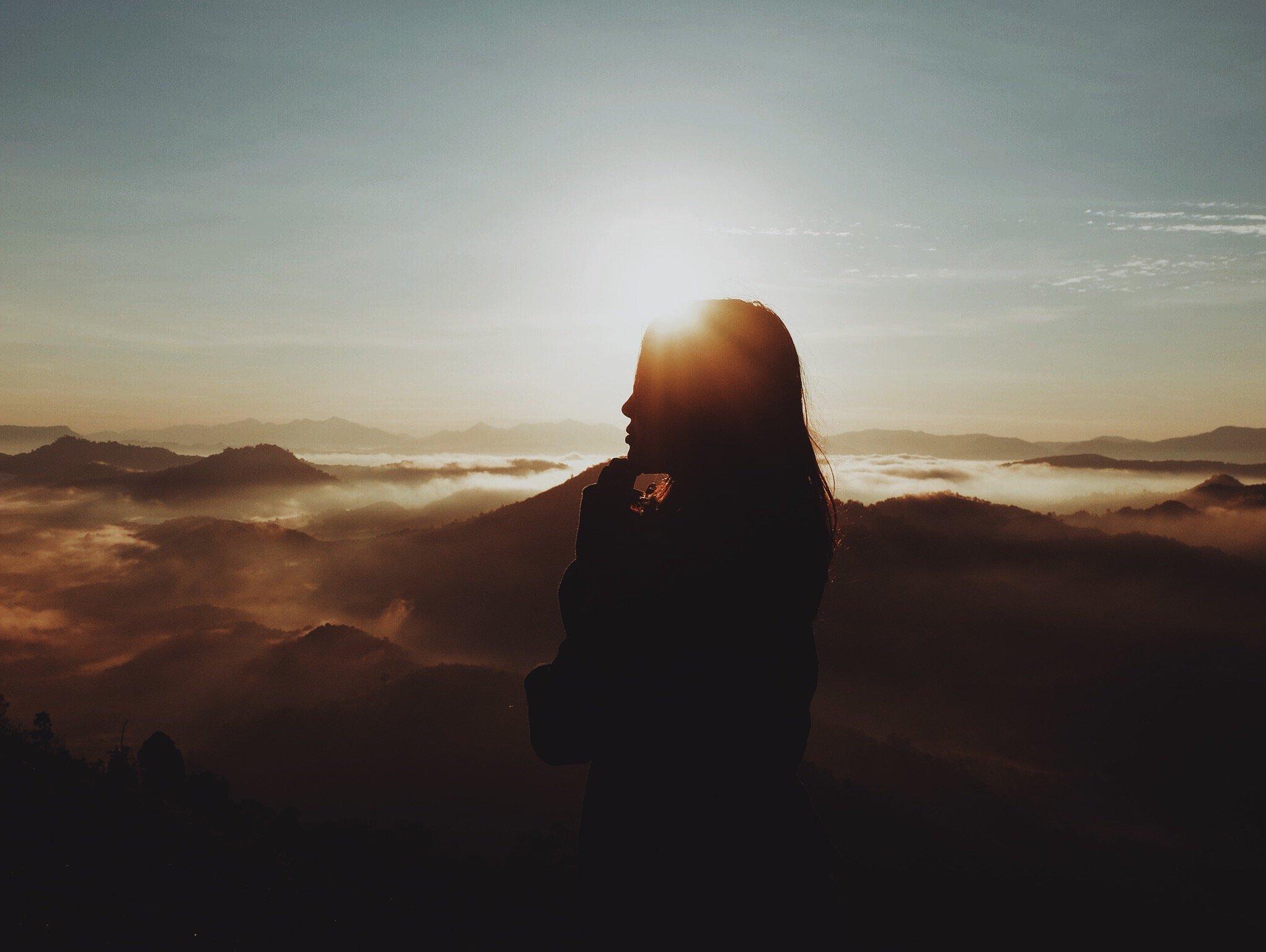 Mulher pensativa no topo de uma montanha