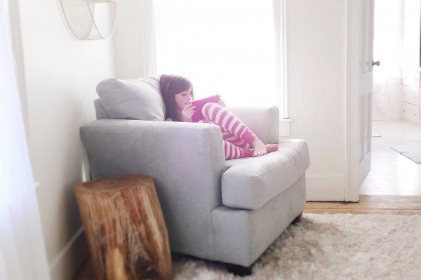 Criança sentada no sofá segurando um tablet