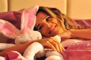 Ingrid Guimarães deitada com coelho de pelúcia em cena do filme 'De Pernas Pro Ar'