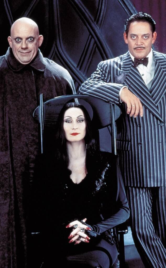 Mulher sentada em uma cadeira com dois homens em cada lado