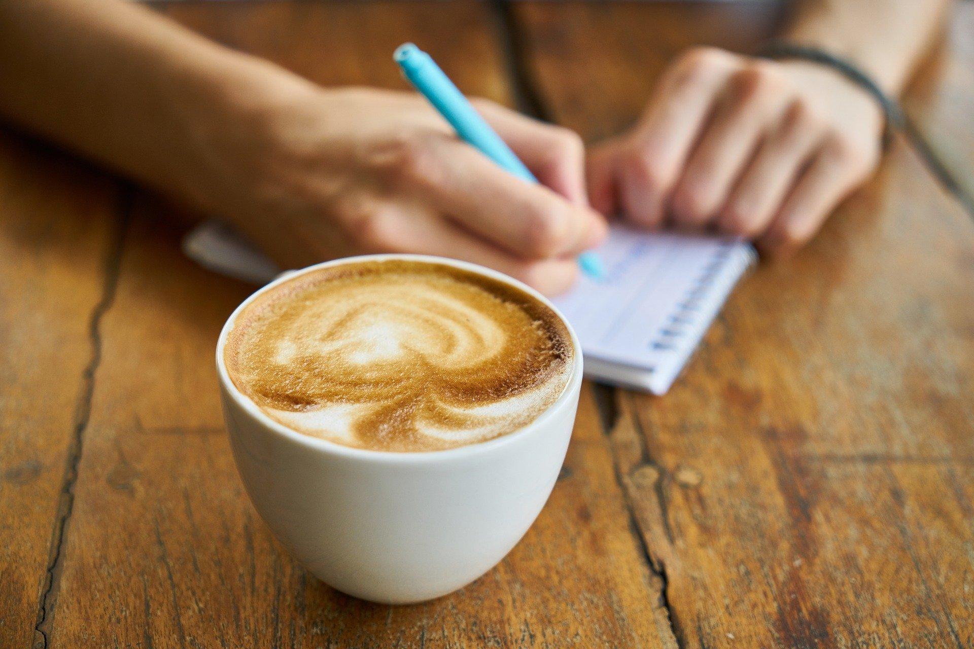 Mulher fazendo uma anotação em uma agendinha ao lado de uma xícara de café