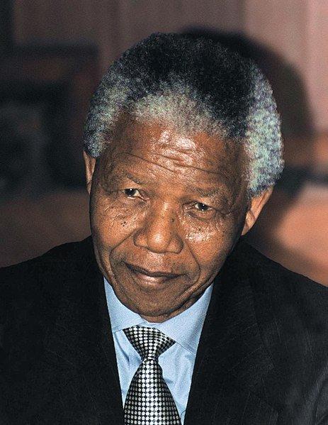 Nelson Mandela sorrindo e olhando para frente