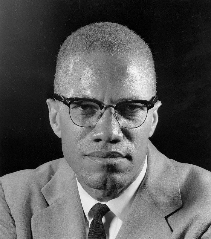 Malcolm X usando terno e gravata em frente a um microfone
