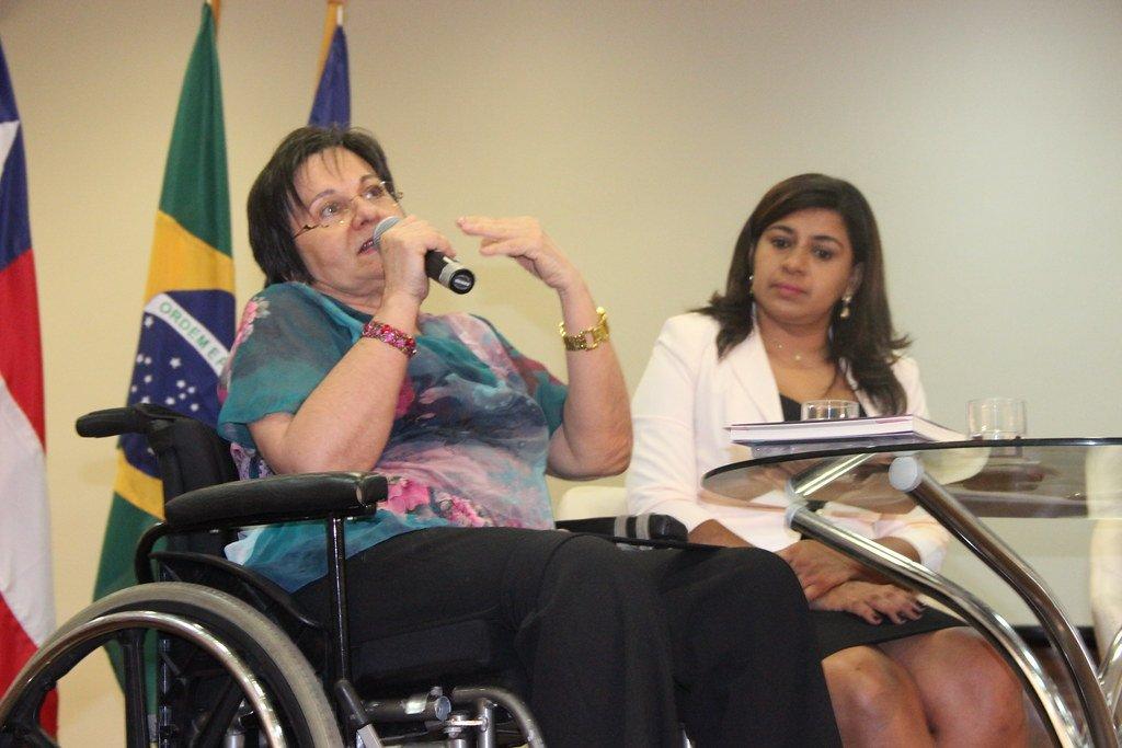 Maria da Penha segurando microfone e falando em sua cadeira de rodas ao lado de outra mulher
