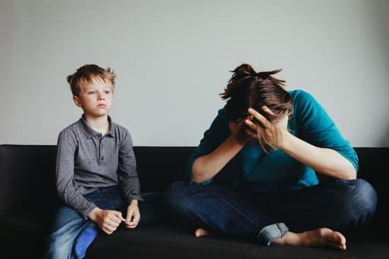 Mulher sentada no sofá com as pernas cruzas e com as mãos no rosto e ao lado uma criança a olhando com tristeza