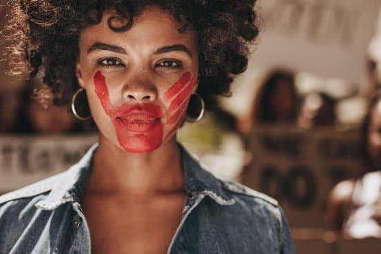 Mulher em protesto com a boca marcada com uma mão