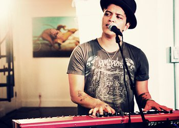 Cantor Bruno Mars vestindo camiseta e chapéu, tocando um teclado vermelho e cantando.