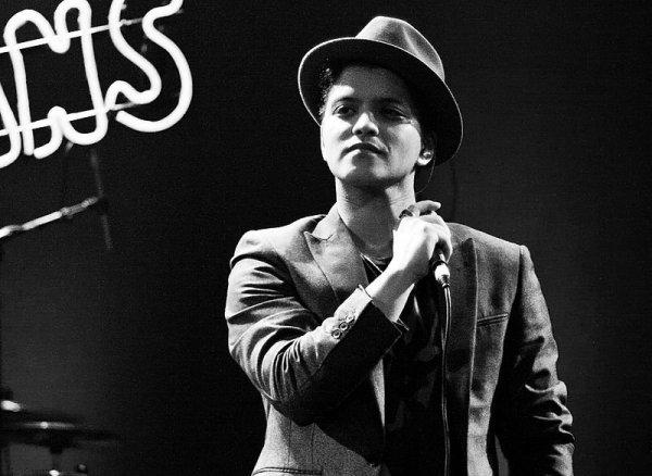 Bruno Mars vestindo terno, gravata e chapéu, segura um microfone durante um show.
