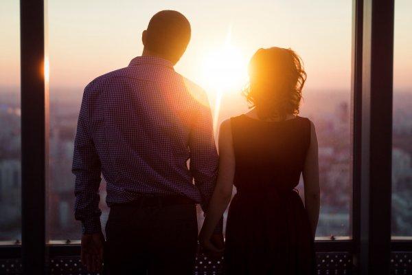 Casal olhando para a janela observando o por do sol