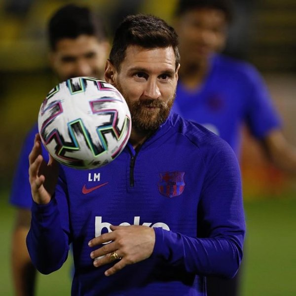 Lionel Messi segurando bola de futebol