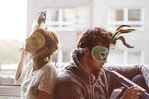 Mulher e homem com máscara de carnaval em uma janela.