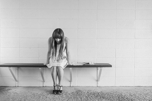 Menina sentada de cabeça baixa em banco