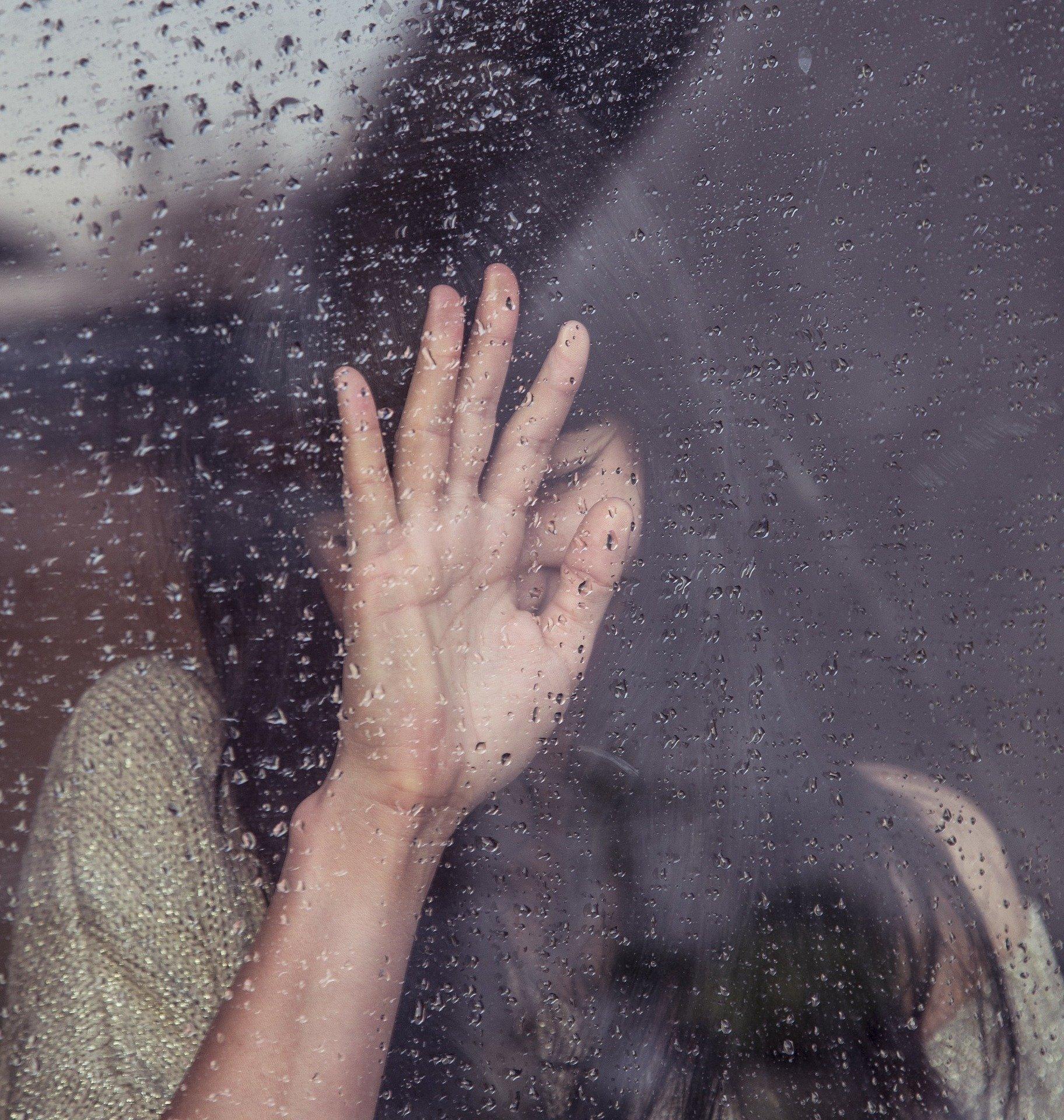 Mulher triste com a mão na janela  com gotas de chuva