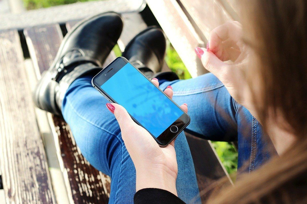 Mulher sentada em um banco de madeira segurando celular