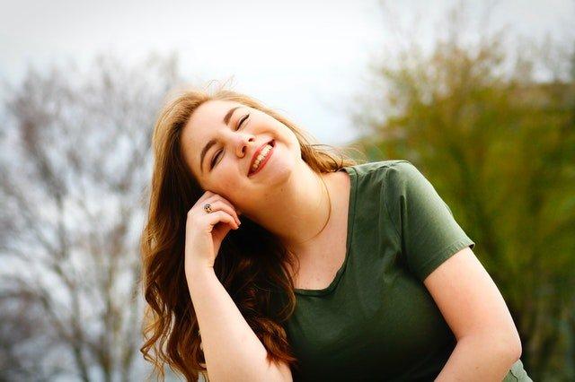 Mulher sorrindo com a mão direita em sua bochecha, em um parque.
