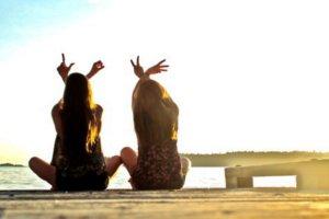Duas amigas sentadas na praia formando a palavra 'love' com as mãos.