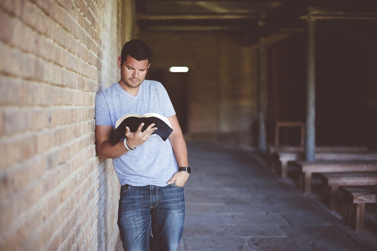 Homem lendo bíblia ao lado da parede a igreja