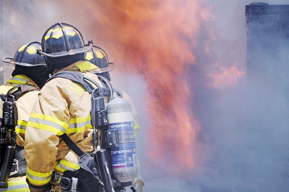 Dois bombeiros e fogo ao fundo