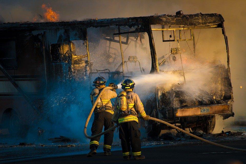 Bombeiros jogando água em ônibus em chamas