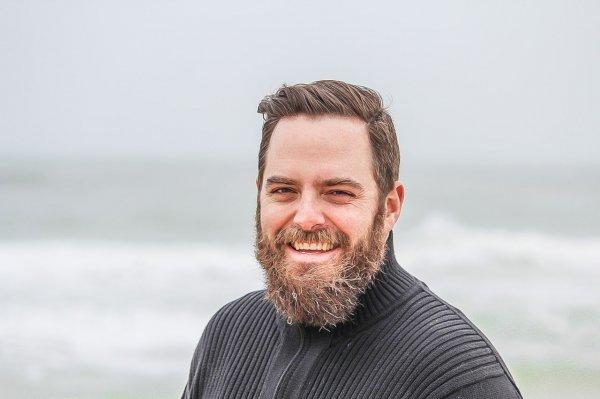 Homem de barba feliz com mar ao fundo