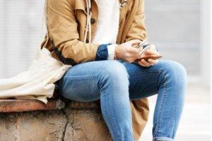 Corpo de homem sentado mexendo no celular
