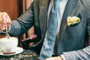 Homem mexendo xícara de café de terno e gravata