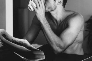 Homem tomando café com caneca na mão e lendo jornal