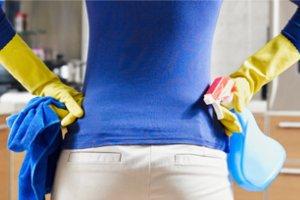 Pessoa com as mãos na cintura segurando produtos de limpeza.