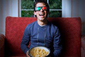 Homem com óculos 3D segurando balde de pipoca ao assistir a um filme.