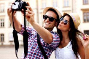 Casal tirando selfie com uma câmera.