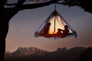 Barraca de acampamento pendurada em uma árvore.
