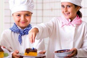Duas crianças com roupas de chef fazendo um bolo.