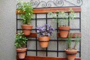 Jardim vertical com vários vasos de flores.