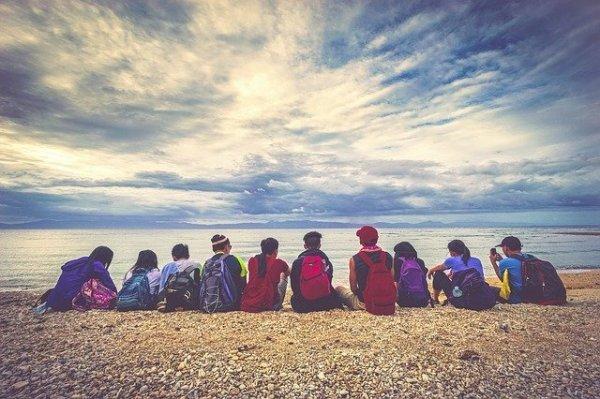 Grupo de pessoas com mochilas sentado lado a lado na areia a beira-mar.