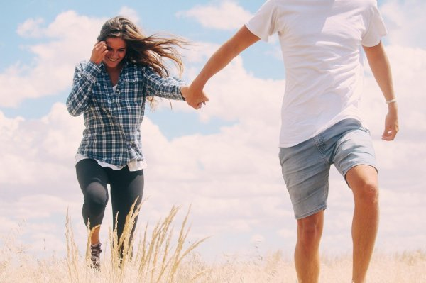 Homem andando na frente, conduzindo mulher pela mão, que sorri enquanto tira o cabelo do rosto com a mão que está livre.