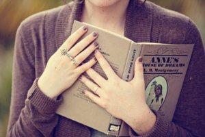 Mulher segurando um livro próximo ao seu corpo.