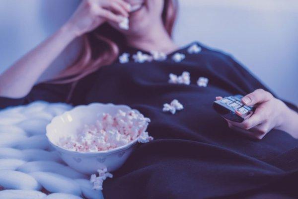 garota comendo pipoca deitada e sorrindo.